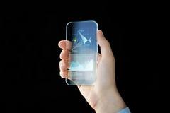 Schließen Sie oben von der männlichen Hand mit transparentem Smartphone Lizenzfreies Stockbild