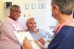 Schließen Sie oben von der männlichen Krankenschwester Updating Patient Notes Stockfoto