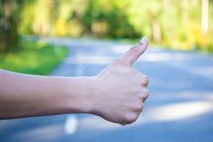 Schließen Sie oben von der männlichen per Anhalter fahrenden Hand stockfoto