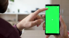 Schließen Sie oben von der Mannhand, die einen Smartphone mit grünem Schirmfarbenreinheitsspott oben auf ihm berührt und verwende stock video