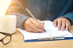 Schließen Sie oben von der Mannhand mit Stift Stockfotografie