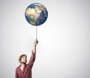 Schließen Sie oben von der menschlichen Hand, die an Erdplaneten hält Stockbilder