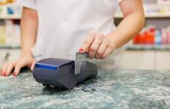 Schließen Sie oben von der menschlichen Hand, die Kreditkarte in Zahlungsmaschine setzt Lizenzfreies Stockbild