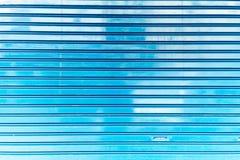 Schließen Sie oben von der Metallrollen-Fensterladentür, von der blauen Metallplattenwandbeschaffenheit und vom Hintergrund, Absc Stockfotos