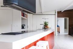 Schließen Sie oben von der modernen Kücheninselbank mit orange Akzentfarbe lizenzfreie stockfotos