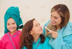 Schließen Sie oben von der Mutter, die ihre Tochterzähne im Badezimmer putzt lizenzfreies stockfoto
