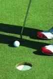 Schließen Sie oben von der Person, die Golfball auf Golfplatz setzt Lizenzfreie Stockfotos