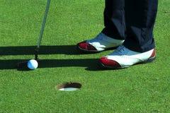 Schließen Sie oben von der Person, die Golfball auf Golfplatz setzt Lizenzfreies Stockfoto