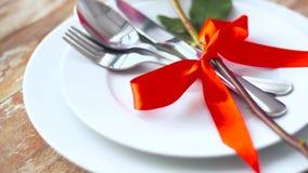 Schließen Sie oben von der Rotrosenblume auf Satz Tellern stock video