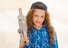 Schließen Sie oben von der schönen gelockten Mädchen wearin Jungenkleidung und vom Halten in ihren Händen eines Spielzeuggewehrs lizenzfreie stockbilder