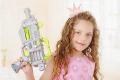 Schließen Sie oben von der schönen gelockten Mädchen wearin Jungenkleidung und vom Halten in ihren Händen eines Spielzeuggewehrs lizenzfreies stockfoto