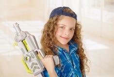 Schließen Sie oben von der schönen gelockten Mädchen wearin Jungenkleidung und vom Halten in ihren Händen eines Spielzeuggewehrs stockfoto
