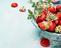 Schließen Sie oben von der Schüssel mit Erdbeeren auf hellblauem rustikalem Hintergrund Stockbild