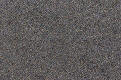 Schließen Sie oben von der schwarzen Sandbeschaffenheit mit farbigen Flecken Lizenzfreie Stockfotografie