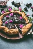 Schließen Sie oben von der selbst gemachten Kirschtorte auf rustikalem Küchentischhintergrund mit Stau und Tischbesteck Sommerbee Stockfotografie