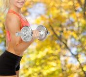 Schließen Sie oben von der sportlichen Frau mit schwerem Stahldummkopf Stockfoto
