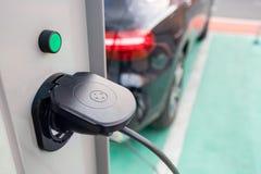 Schließen Sie oben von der Stromversorgung, die in ein Elektroauto verstopft wird, das aufgeladen wird Ladestation des elektrisch lizenzfreie stockfotos