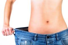 Schließen Sie oben von der Taille einer Frau innerhalb der Blue Jeans Stockfotografie