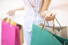 Schließen Sie oben von der vielen Holdinghand der jungen Frau der Verbraucherschutzbewegung Einkaufstasche in Mode stockbild