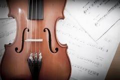 Schließen Sie oben von der Violine auf dem links mit unscharfer Musik Stockbilder
