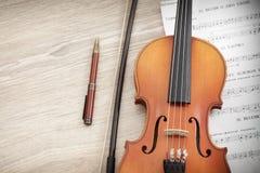 Schließen Sie oben von der Violine mit Musikbuch und Bleistift Lizenzfreie Stockfotografie