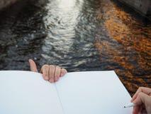 Schließen Sie oben von der weiblichen Hand, die einen Stift hält und öffnete Sketchbookseiten auf dem Stadtkanalhintergrund stockfotos