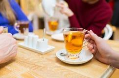 Schließen Sie oben von der weiblichen Hand mit Teeschale am Café Stockfotografie