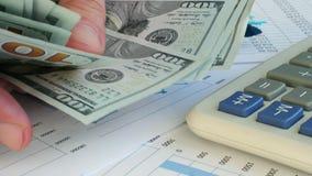 Schließen Sie oben von der Zählung des Bargeldes auf Schreibtisch stock video footage