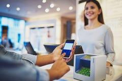 Schließen Sie oben von der Zahlung mit Handy Lizenzfreie Stockfotos