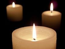 Schließen Sie oben von drei beleuchteten Kerzen auf schwarzem Hintergrund. Lizenzfreie Stockbilder