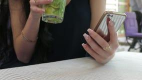Schließen Sie oben von ein Frau ` s Händen unter Verwendung Smartphones und des Trinkens eines Cocktails stock footage