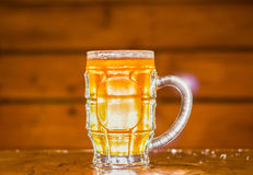 Schließen Sie oben von einem blonden Handwerksbier, das in ein Pint-Glas auf hölzernem Hintergrund gefüllt wird lizenzfreie stockfotografie