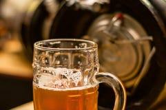 Schließen Sie oben von einem blonden Handwerksbier, das in ein Pint-Glas auf unscharfer Tabelle gefüllt wird lizenzfreies stockbild