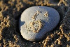 Schließen Sie oben von einem Felsen auf einem sandigen Strand Stockfoto