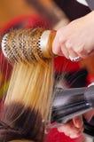 Schließen Sie oben von einem Friseur, der blondes Haar mit Haartrockner und Rundbürste in einem unscharfen Hintergrund trocknet Stockbilder