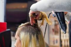 Schließen Sie oben von einem Friseur, der blondes Haar mit Haartrockner und Rundbürste in einem unscharfen Hintergrund trocknet Lizenzfreie Stockfotos