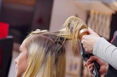 Schließen Sie oben von einem Friseur, der blondes Haar mit Haartrockner und Rundbürste in einem unscharfen Hintergrund trocknet Lizenzfreies Stockbild