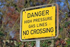 Schließen Sie oben von einem gelben Warnzeichen im Freien, das dager Hochdruckgasleitung keine Überfahrt sagt stockbild