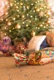 Schließen Sie oben von einem Geschenk vor einem Weihnachtsbaum lizenzfreie stockfotos