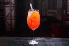 Schlie?en Sie oben von einem Glas aperol spritz das Cocktail und auf dem Barz?hler, auf einem roten hellen Hintergrund stehen stockfoto