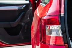 Schließen Sie oben von einem hinteren Autolicht Rotes Auto mit offener Seitentür und Stamm Lizenzfreie Stockfotografie