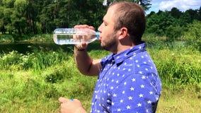 Schließen Sie oben von einem jungen Mann in blaues T-Shirt Trinkwasser und vom Aufenthalt nahe Fluss im Wald