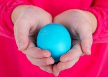 Schließen Sie oben von einem Kind, das ein Osterei anhält Lizenzfreies Stockfoto