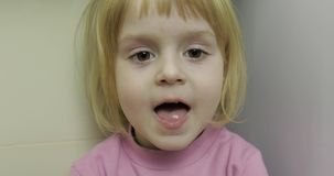 Schließen Sie oben von einem kleinen blonden netten Mädchengesicht Lokalisiert auf Weiß inside Brunettefrau, blaue Augen stock video