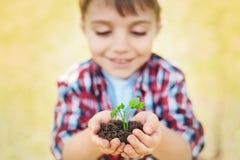 Schließen Sie oben von einem kleinen Jungen, der Handvoll Boden hält Stockbild