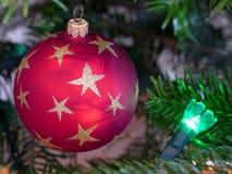 Schließen Sie oben von einem kreisförmigen roten Flitter auf einem Weihnachtsbaum mit einem grünen feenhaften Licht lizenzfreie stockbilder