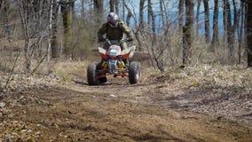 Schließen Sie oben von einem Mann, der ATV reitet und mit hoher Geschwindigkeit entlang der Straße im Waldreiter umzieht, der um  stock footage