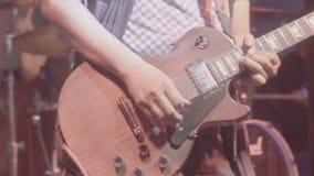 Schließen Sie oben von einem Mann, der eine Gitarre während eines Liveauftritts mit ändernden Farbstadiumslichtern spielt stock video footage