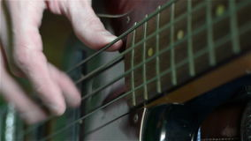 Schließen Sie oben von einem Mann, der einen E-Gitarren-Baß spielt stock video