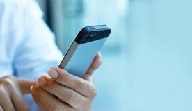 Schließen Sie oben von einem Mann, der intelligentes Mobiltelefon auf Pastellfarbton verwendet Stockfotos